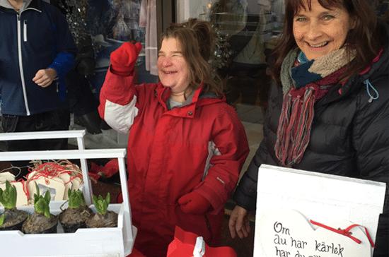 Bild från förra årets julmarknad. Glad tjej i röd jacka arbetar i marknadsståndet.