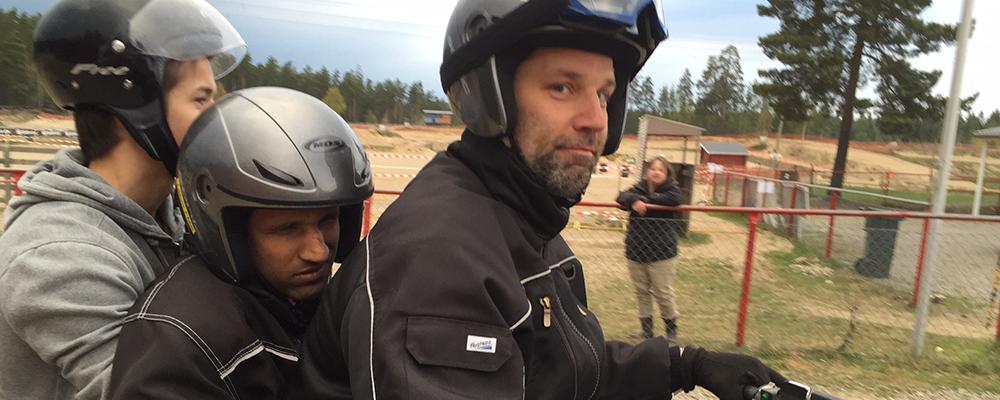 Tre killar startfärdiga på en fyrhjuling.