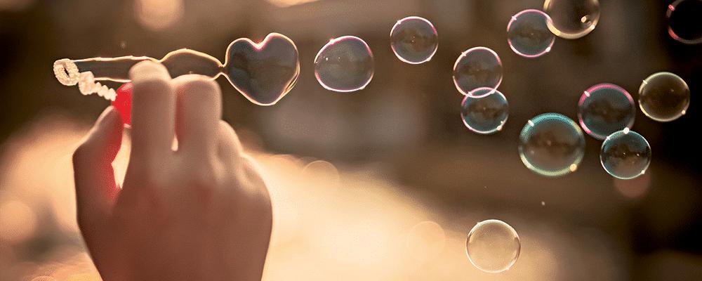 Hand och såpbubblor, en såpbubbla formad som ett hjärta.