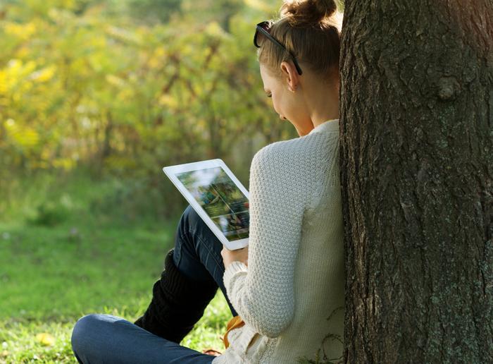 Tjej läser under träd